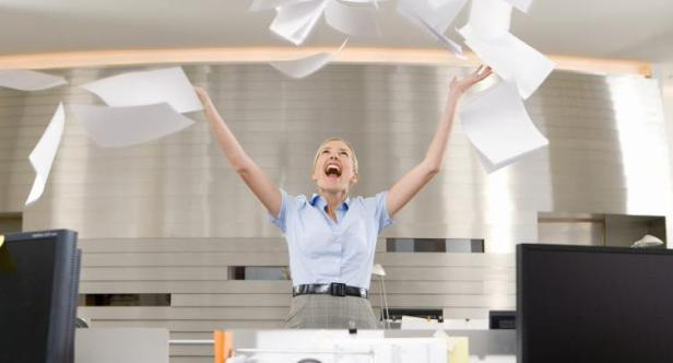 Businesswoman throwing paper up in office, arms raised, smiling, low angle view